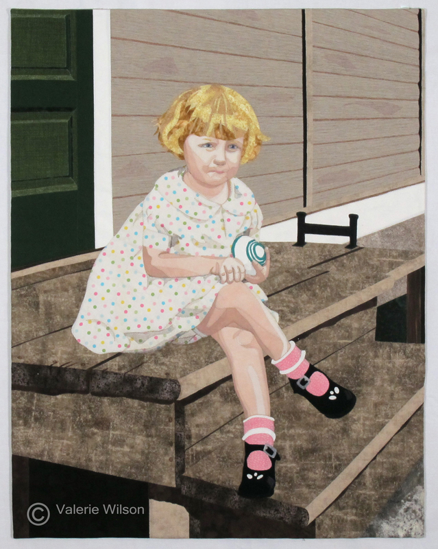 An art quilt with a blonde little girl,sitting on a wooden step, holding a toy.Commercial and hand-dyed cottons. Valerie Wilson 2015.